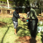 Prof Esther Magiri, planting a tree during the commemoration.