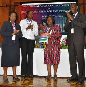 Dr.-Peggy-Oti-Boateng-second-right-displays-the-newly-launched-Journal-of-Sustainable-Research-in-Engineering.-She-is-joined-by-Prof.-Mabel-Imbuga-left-and-College-of-Engineering-and-Technology-Principal-Prof.-Bernard-Ik