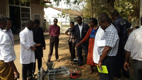 Eric Kimathi and Dennis Katana demonstrating how their charcoal briquetting machine works