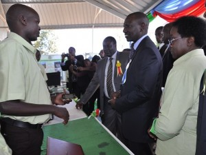 Mr. Okello (left) explains how  M-shamba works to Deputy President  William Ruto and the Vice Chancellor Prof. Mabel Imbuga during the Nyeri ASK Show last year.