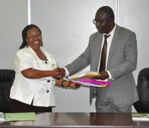Prof. Ngumi (left) hands over documents to Prof. Moirongo