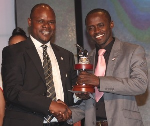 Dr. Weweru (right) recives his Award trophy from Vice Chair, Kenya Footbal Federation, Robert Asembo