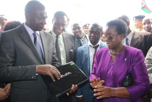 Prof. Mabel Imbuga (right) introduces the JKUAT assembled lap top to Hon. William Ruto (left) and Prof. Jacob Kaimenyi