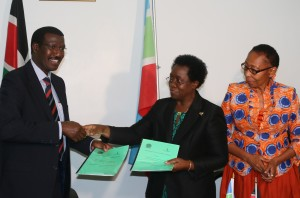 Dr. Chumo (left) and Prof. Imbuga exchanging the partnership documents, witnessed by Deputy Vice Chancellor (RPE) Prof. Esther Kahangi.