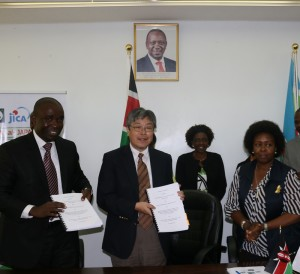 Mr Wamalwa (left) and Mr Eguchi display the signed contract documents. Looking on is Ms Muraguri(right) and Ms Dena (back).