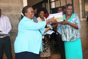 Teacher Lucy Kinuthia (right) receives part of the books donation from Prof Ngumi.
