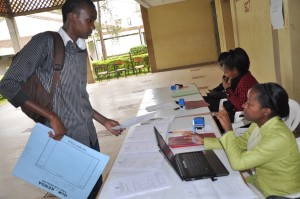 Ms. Donna Onserio assists Alloys Mutwiri (left) to register at the School of Computing and Information Technology