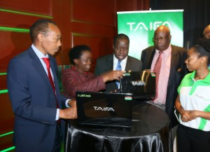 Prof. Mabel Imbuga (second left) takes Dr. Matiang'i through the Taifa Laptop as JKUAT Chancellor, Prof. Maloiy (second right) and Kimbu Deputy Governor, Gerald Githinji (left) follow