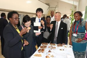 Prof. Imbuga (left) and Mr. Yano (right) have a taste of cricket and cricket products during the Expo