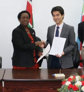 Prof. Imuga (left) and Tsuyoshi exchange partnership documents for construction of the factory