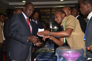Robbin Mureithi explains to the Deputy President William Ruto how his innovation works during the Kenya Water Week, 2016