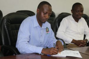 Dr. Orwa putting pen to paper as he accepts his new position