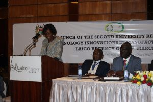 Dr. Kopiyo gives her address during the launch of the Reasearch Chair on Technology Innovations in Manufacturing as Dr. Rugutt (right) and other guests follow
