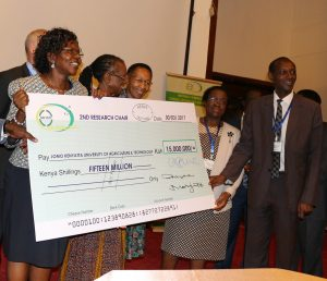 Dr. Kopiyo presents a dummy cheque to JKUAT team led by Vice Chancellor, Prof. Mabel Imbuga (second right)