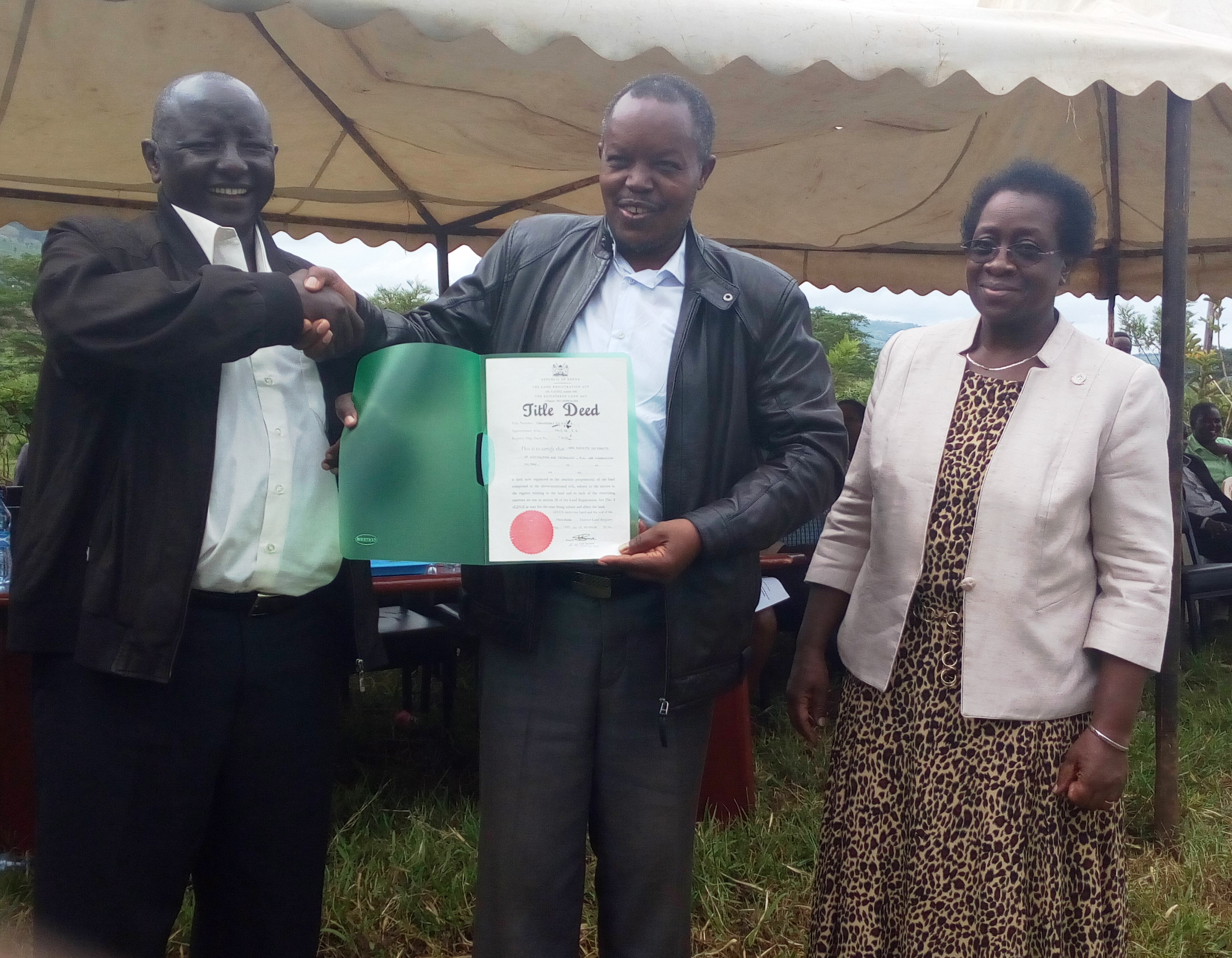 Council Chair Prof. Kanyari receives the Title Deed as Prof. Imbuga looks on.