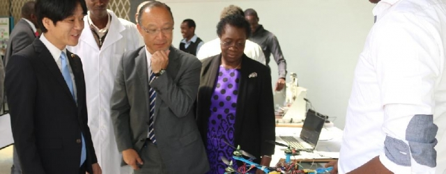 Mr. Horoyuki Yoshiie (Left) Japan, State Minister of Education, Culture, Sports, Science and Technology marvels at a student's innovation during his recent visit to JKUAT. Looking on is AFRICA-ai-JAPAN Project Chief Advisor, Prof. Manadu Tsunoda (center) and Vice Chancellor, Prof. Mabel Imbuga.